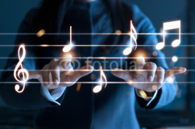 Naklejki Woman hands playing music notes on dark background, music concept