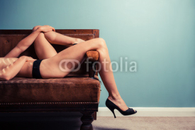Naklejki Sexy young woman in heels on a sofa