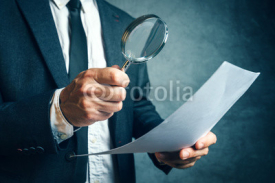 Fototapety Tax inspector investigating financial documents through magnifyi