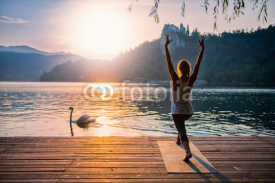 Naklejki Sun Salute Yoga. Young woman doing yoga by the lake at sunset, swan passing by