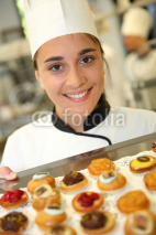 Naklejki Cheerful pastry cook holding tray of pastries