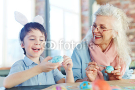 Little boy and senior female making Easter eggs for holiday