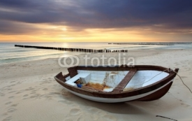 Obrazy i plakaty Boat on beautiful beach in sunrise