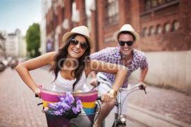 Fototapety Happy couple cycling in the city