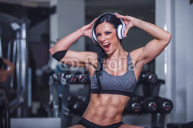 Obrazy i plakaty Crazy fit girl posing in gym with headphone.