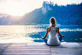 Fototapety Yoga lotus. Young woman doing yoga by the lake, sitting in lotus.