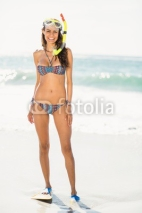 Naklejki Young woman wearing flippers at the beach