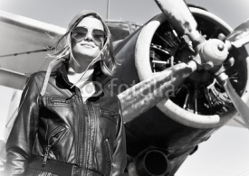 Naklejki Young beautiful woman pilot in front of  airplane.