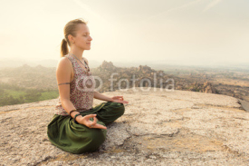 Fototapety Young woman meditating at mountain cliff on sunrise