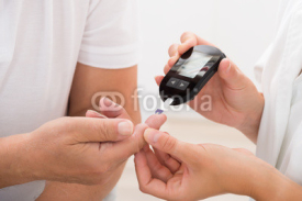 Obrazy i plakaty Doctor Using Glucometer On Patient's Finger