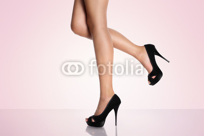 legs with black high-heeled shoes on a pink background
