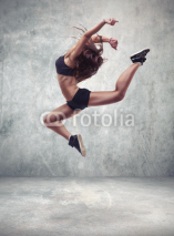 Naklejki young woman dancer with grunge wall background
