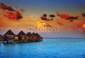 Naklejki houses on piles on water at the time sunset