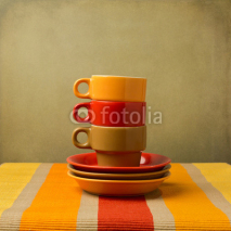Naklejki Stack of colorful coffee cups on tablecloth or place mat