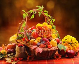 Naklejki Wicker basket with autumn fruits and flowers