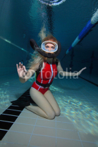 Naklejki Female scuba diver with red swimsuit diving in the pool