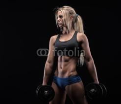 Obrazy i plakaty Young woman lifting the dumbbells