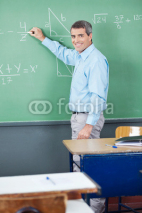 Naklejki Portrait Of Mature Teacher Writing On Board