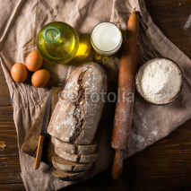 Naklejki Still life photo of bread and flour with milk and eggs at the wo