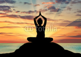 Fototapety Silhouette of a girl practicing yoga