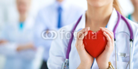 Obrazy i plakaty Female doctor with stethoscope holding heart