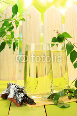 Naklejki Glasses of birch sap on green wooden table